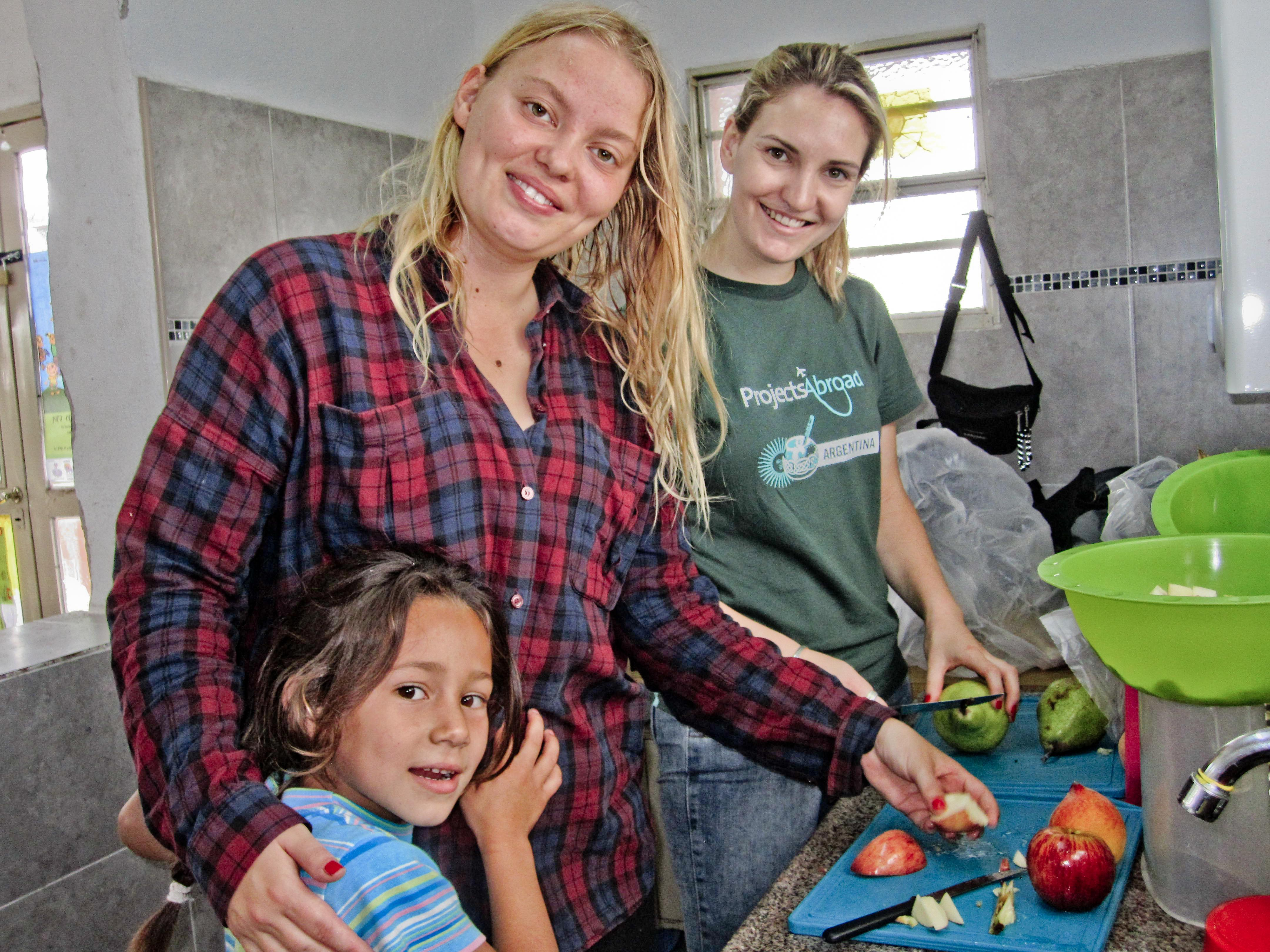 Projects Abroad volunteer working with children in Argentina prepares fruit in dining halls during a Childcare project.